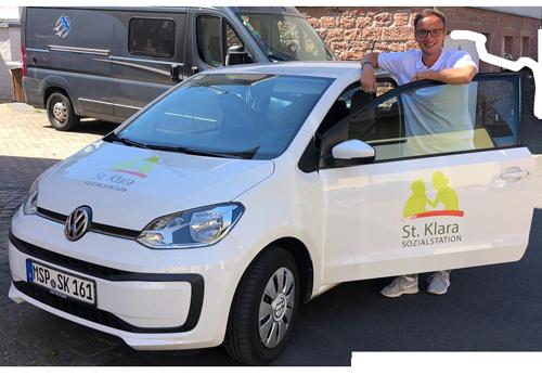 Oliver Goßmann steht glücklich am Dienstwagen der Sozialstation Kothe.