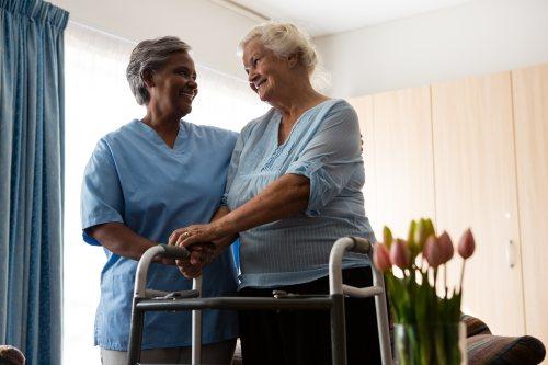 Altenpflegerin unterstützt zufriedene Kundin beim Gang am Gehbock.