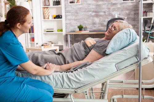 Altenpflegerin versorgt freundliche Kundin mit liegender Infusion in häuslichem Umfeld.