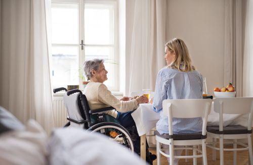 Altenpflegerin unterstützt Kundin freundlich bei der Nahrungs,- und Flüssigkeitsaufnahme.