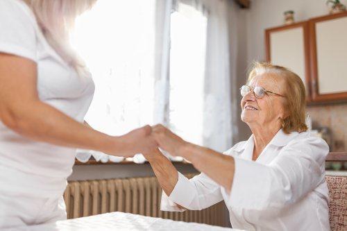 Altenpflegerin unterstützt glückliche Patient beim Transfer vom Sitz in den Stand in ihrem Zuhause.