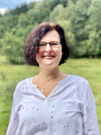 Angelika Brod zeigt sich fröhlich auf einer Wiese im Grünen als Teammitglied und Pflegedienstleitung in der Sozialstation Kothe.