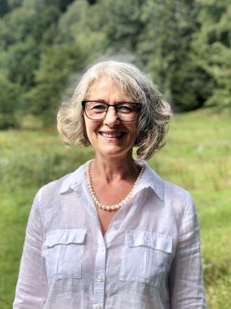 Anja Kothe zeigt sich fröhlich in Dienstkleidung als Inhaber und Geschäftsführer der Sozialstation Kothe.