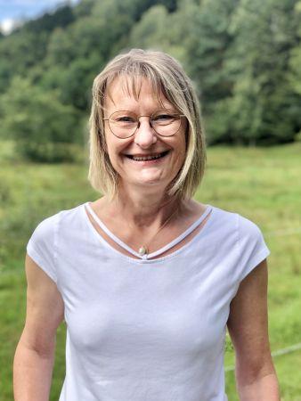 Annette Fleckenstein zeigt sich fröhlich in Dienstkleidung als Mitarbeiterin der Sozialstation Kothe.