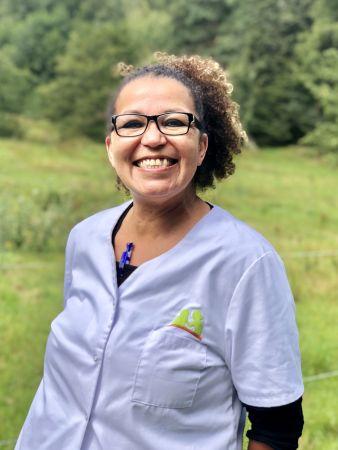 Annette Onyedimazu-Runge zeigt sich fröhlich in Dienstkleidung als Mitarbeiterin der Sozialstation Kothe.