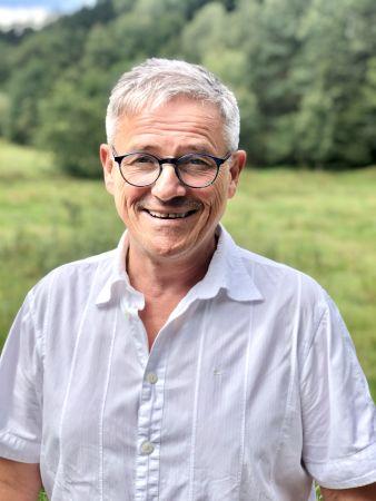 Dieter Kothe zeigt sich fröhlich in Dienstkleidung als Inhaber und Geschäftsführer der Sozialstation Kothe.