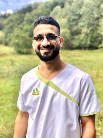 Hussein Saleh zeigt sich fröhlich in Dienstkleidung als Mitarbeiterin der Sozialstation Kothe.