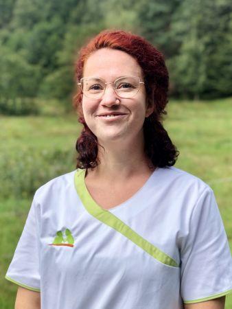 Melanie Zaloga zeigt sich fröhlich in Dienstkleidung als Mitarbeiterin der Sozialstation Kothe.