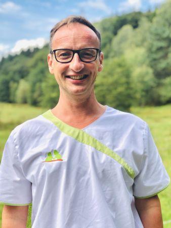 Oliver Goßmann zeigt sich fröhlich in Dienstkleidung als Mitarbeiterin der Sozialstation Kothe.