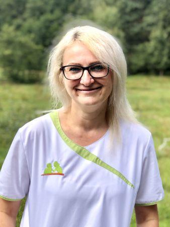Wieslawa Brzozka zeigt sich fröhlich in Dienstkleidung als Mitarbeiterin der Sozialstation Kothe.