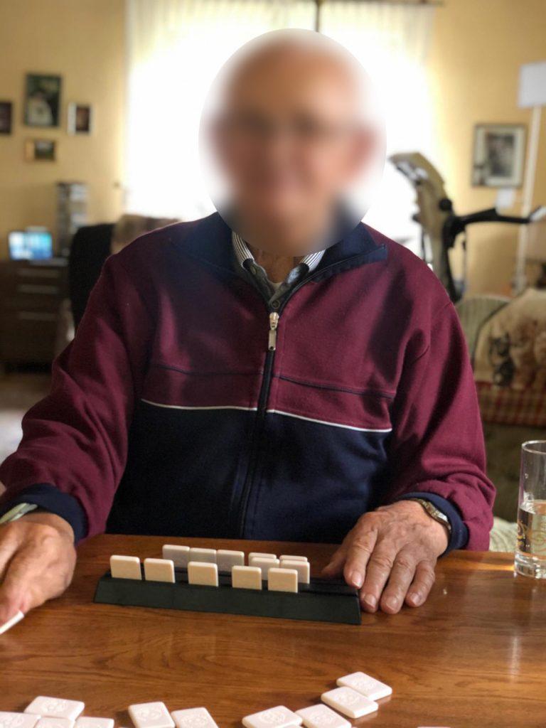 Älterer Mann sitzt am Tisch und spielt Rummy Cup. Er trägt einen rot blauen Jogginganzug und lächelt dabei.